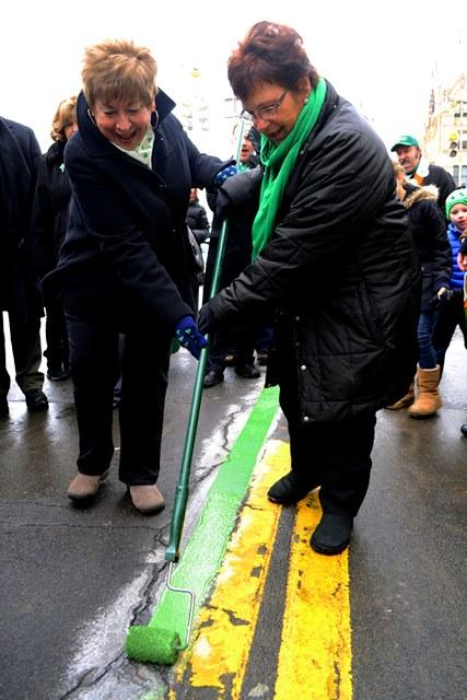 Mary Ann Fountain and Kathy Schwanke, grand marshalls in the St. Patrick's Day parade, help paint the route's green stripe.