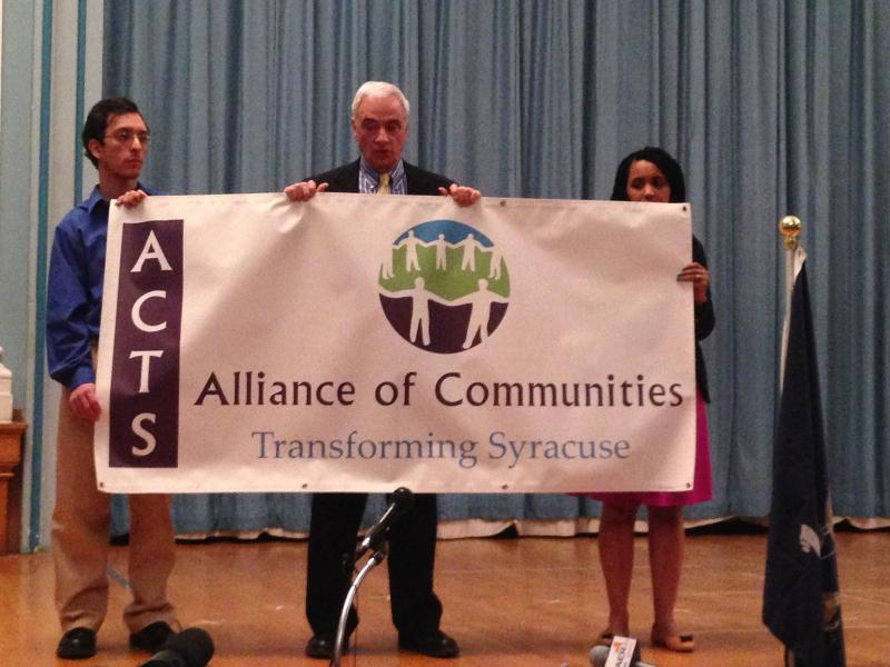 Supporters of pre-K, including Syracuse Common Councilor Nader Maroun,  hold up banner at news conference Thursday.