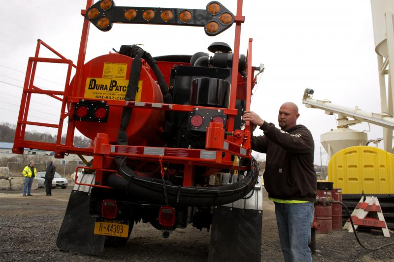 Kevin Hunter, a Syracuse public workers employee, prepares the city's new pothole patching truck.