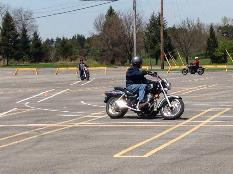 Motorcyclists operate their bikes on the training course.