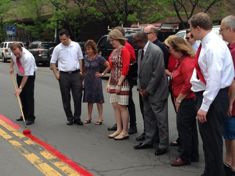 ACR Health Executive Director Michael Crinnin paints a red line down S. Salina Street as part of the outreach effort.