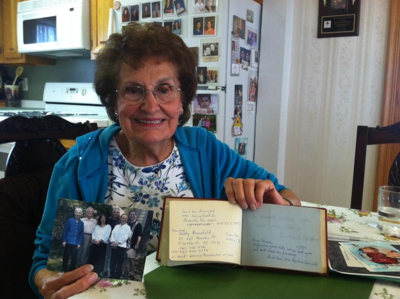 Francis Enwright, 88, poses with her autograph book, signed by Eva, and a photo of Eva with her family.
