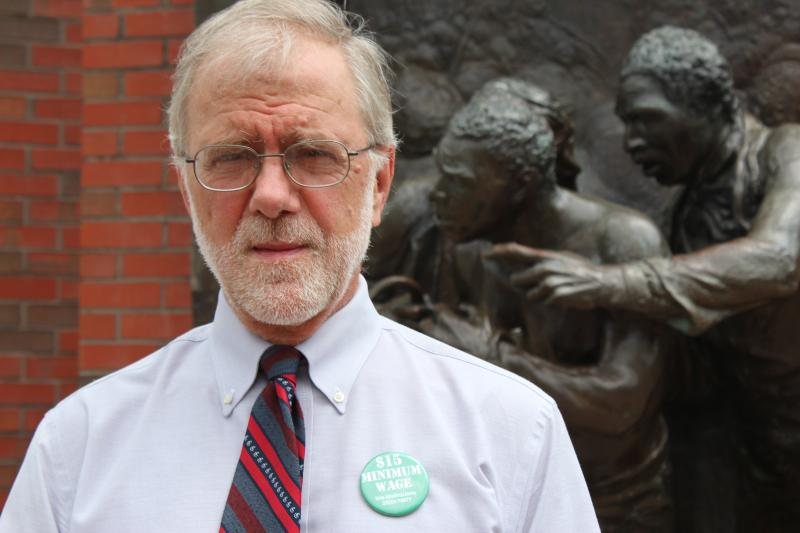 Howie Hawkins speaks to the press in front of the Jerry's Rescue statue in downtown Syracuse.