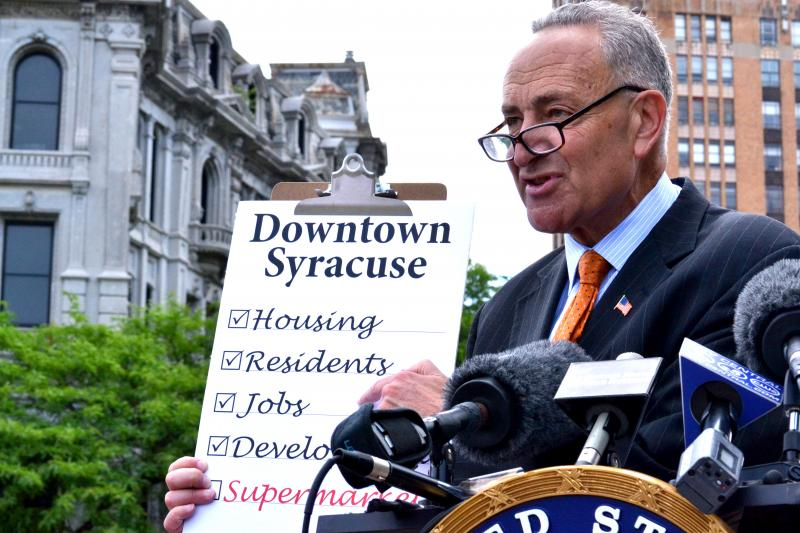 Sen. Charles Schumer, D-N.Y., hold up a symbolic checklist for downtown Syracuse's needs.