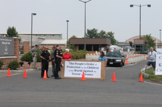 Police stand close to one of the signs brought by protesters and displayed near the Hancock Field Air National Guard Base.