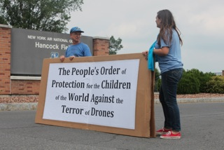Activists stand near the Hancock Field Air National Guard Base to protest drone use.