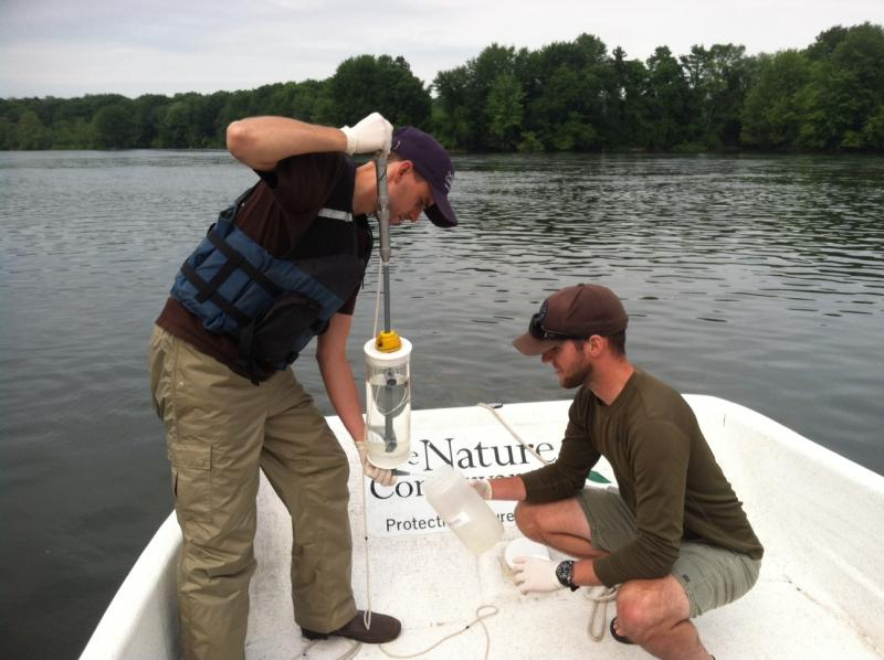 The Nature Conservancy's Andrew Tucker empties water from a collection tube into a container held by Benjamin Wegleitener.
