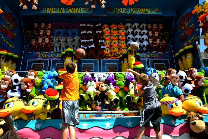 Nine-year-old Kacen Chigaridis, left, and his brother Kyler, 7, play a game on this midway at the New York State Fair.