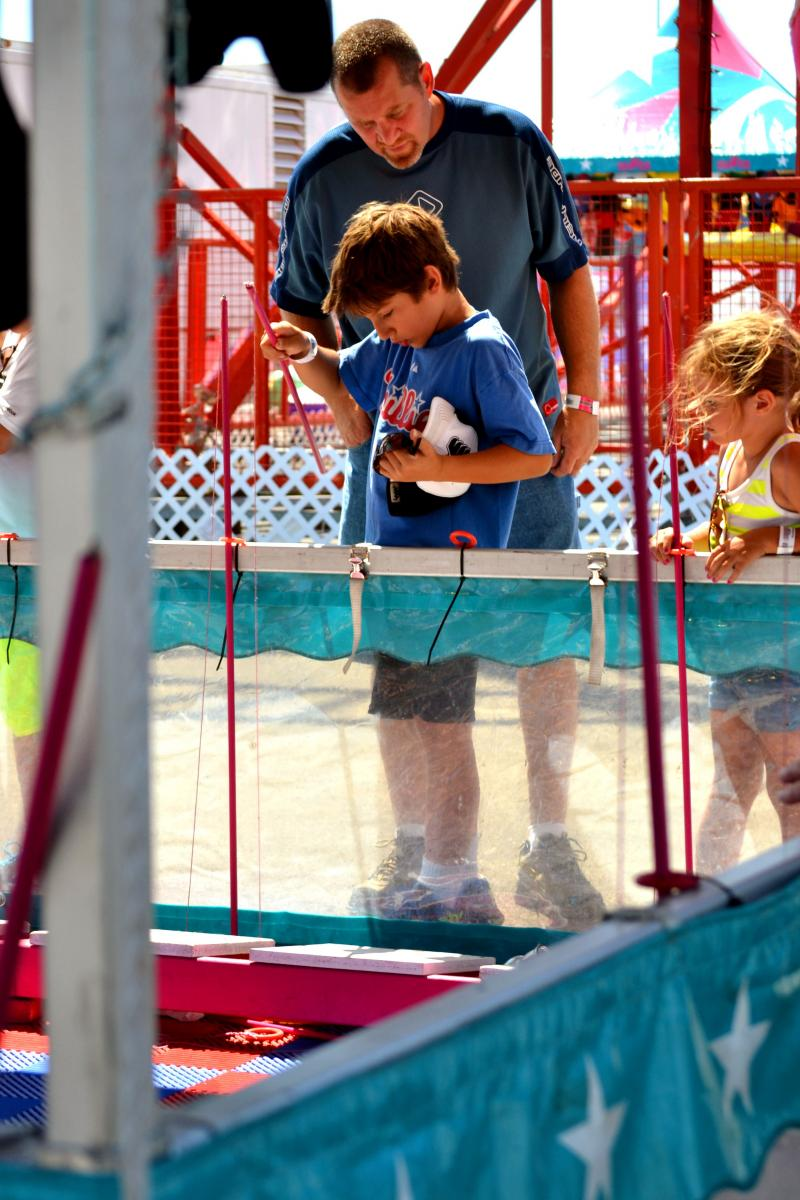 Bob Temble watches his nephew, Tyler Collins, play Bottle Up at the state fair.