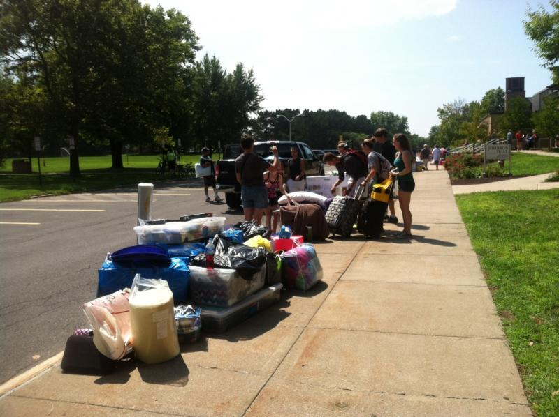 Students leave their belongings on the sidewalk while they wait for help moving into their dorm rooms.