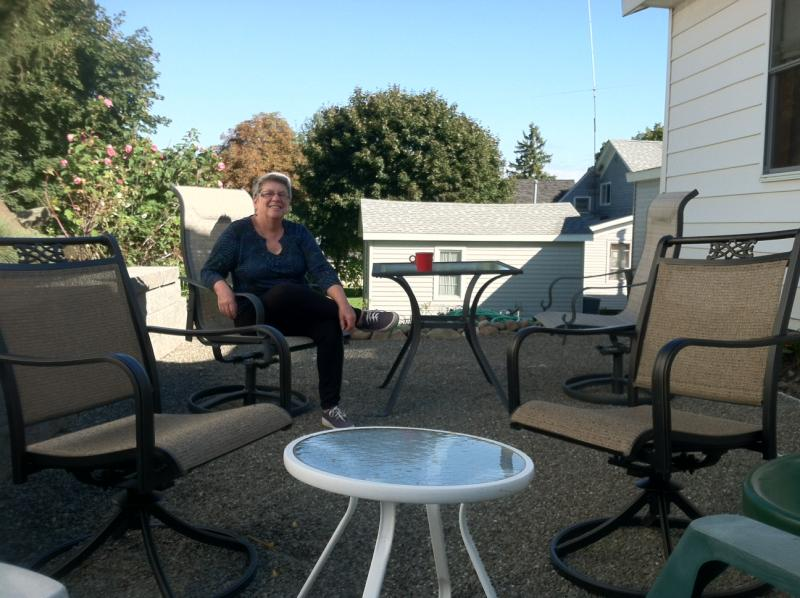 Catharine Early sits in her new outdoor patio. The stone area was one of several projects Early completed this summer.