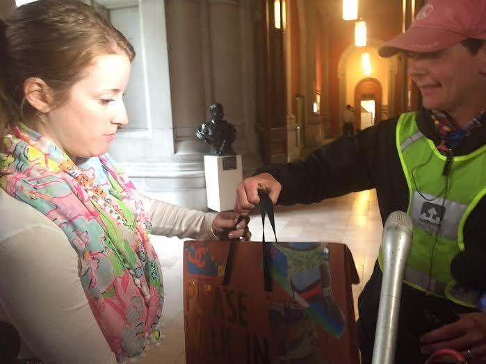 Math teacher Maria DeAngelo (right) delivers student essays and art work to an aide to Gov. Andrew Cuomo. DeAngelo walked 150 miles to protest the governor's education policies.