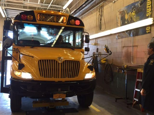 Mike Nuber of New York State Department of Transportation inspects the lights on a school bus.