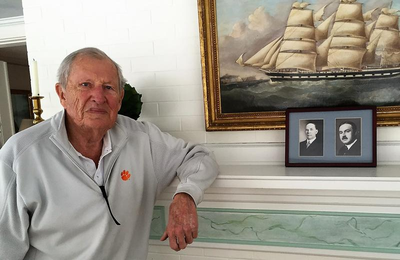 George Couch, long-time member of the club, stands next to pictures of his grandfathers, who were both members of the Black River Valley Club.
