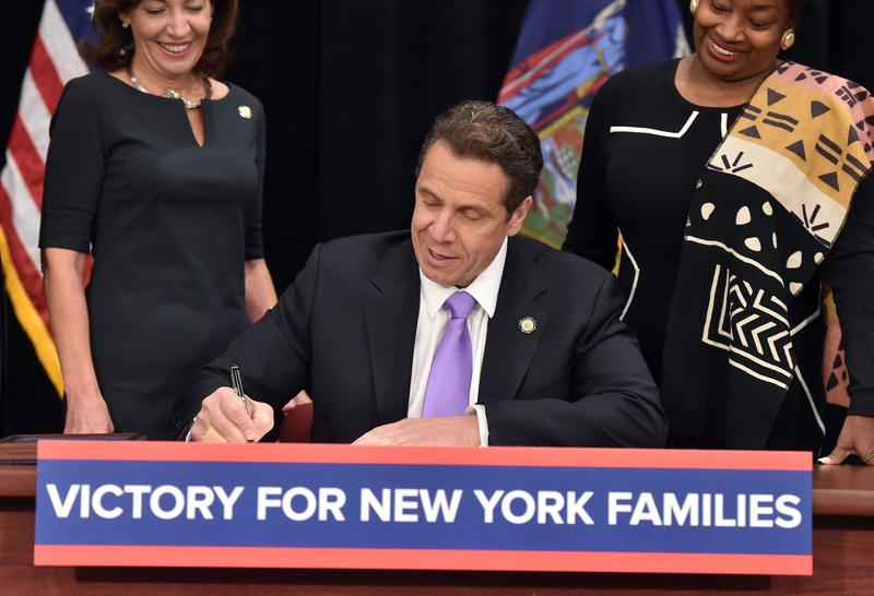 Gov. Andrew Cuomo signing an increase in the minimum wage and the creation of paid family leave.