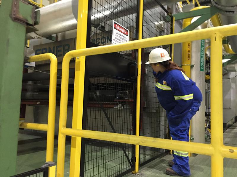 Novelis engineer Teresa Santoferrara inspects the metal furnace at the Oswego County plant.