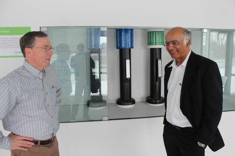 Institute for Energy and Environmental Research President Arjun Makhijani (right) looks at geothermal pipes at the Syracuse Center of Excellence.