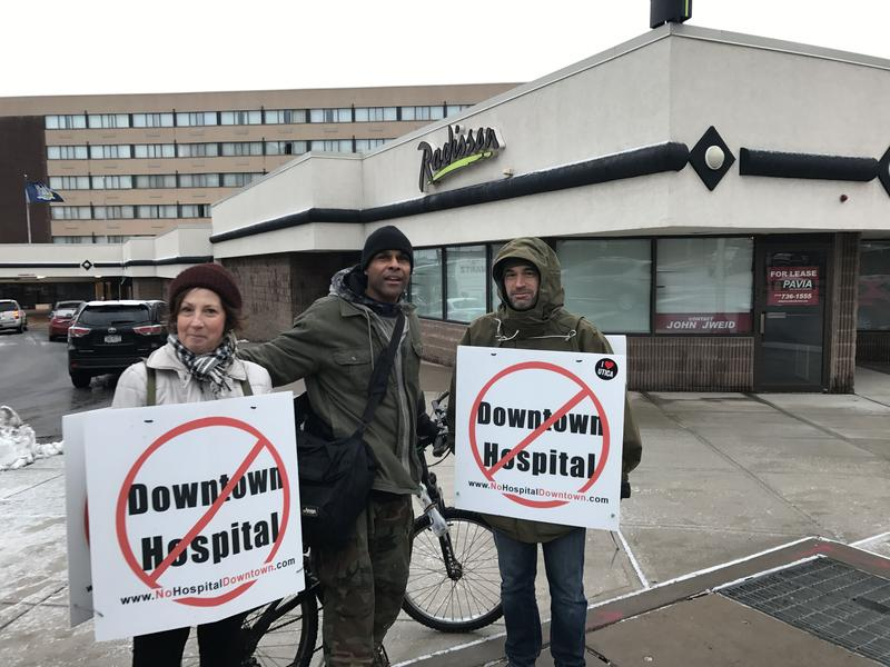 Outside of a legsialtive forum, Donna Beckett, David Michael Carter and Brett Truett voice their opposition to a proposed downtown hospital in Utica.