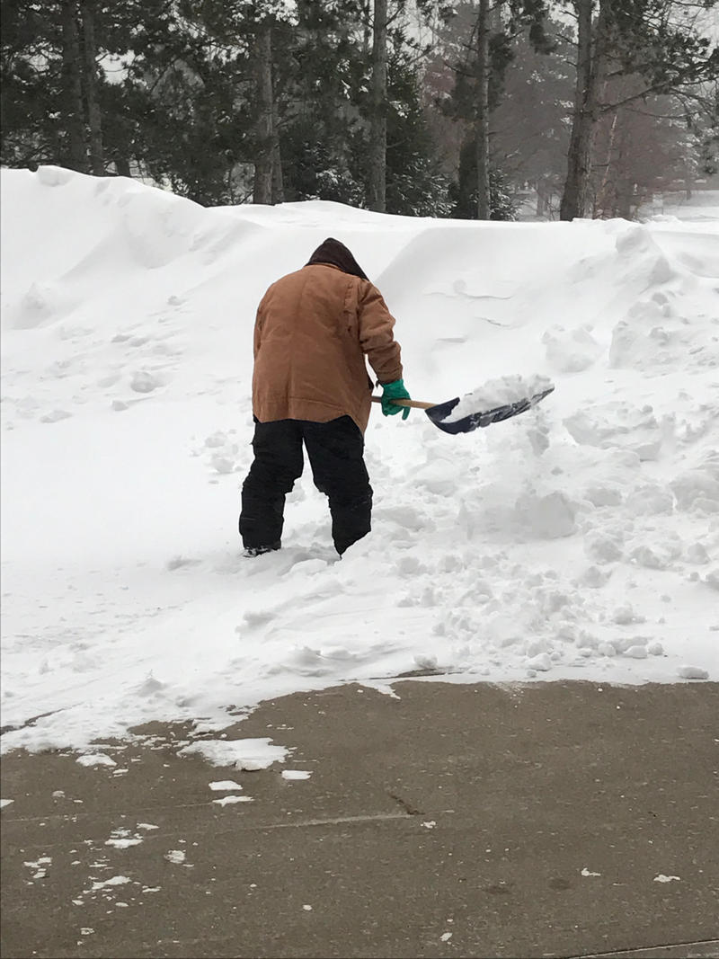 A worker shovels snow on the SUNY Oswego campus Wednesday, after more than a foot of snow fell Tuesday