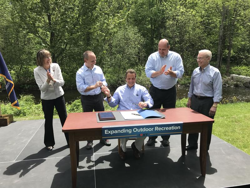 In front of the Salmon River, Gov. Andrew Cuomo approves the acquisition of 6,000 acres of Oswego County land to preserve and maintain the resource.