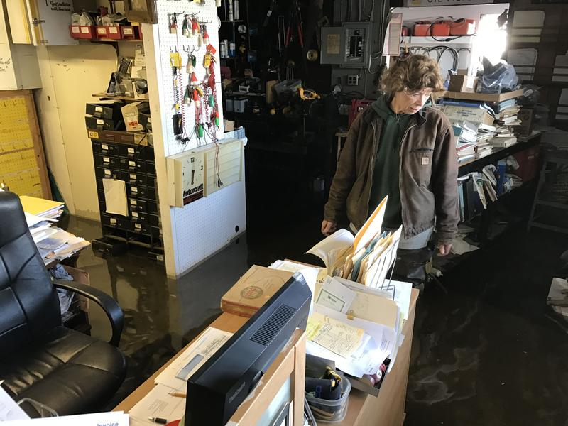 Co-owner of the Greene Point Marina in Sandy Creek, Cathy Goodnough, surveys the flooding damage in her office from Sandy Pond.