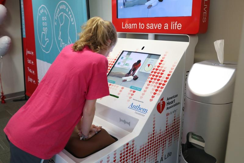 A girl practicing CPR at an automated training kiosk
