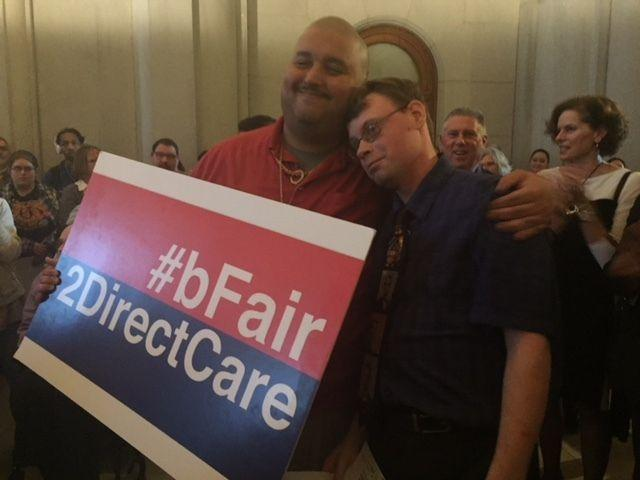 Victor Colon and Mike Brooks, self advocates for the disabled, rally for better pay for their caregivers at the Captial on Wednesday.
