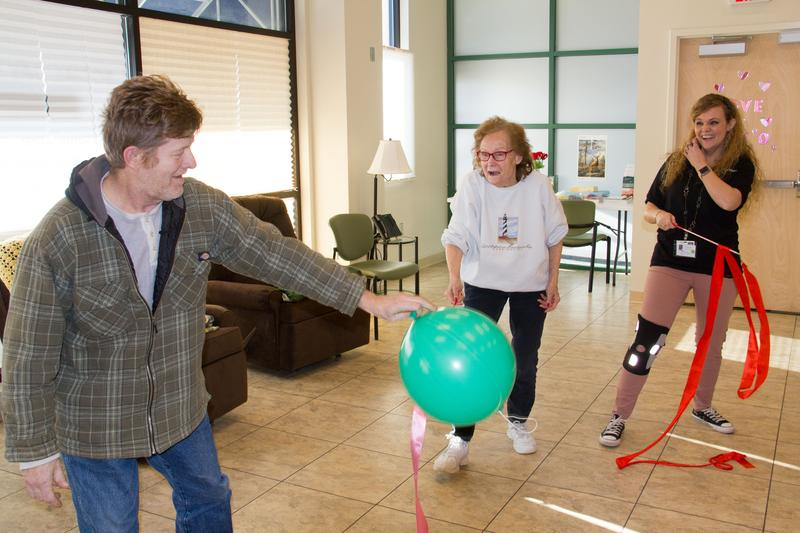 Mike Krause, who suffers from dementia, plays with Joan DeYulio, center, at the Cornerstone Club - a social adult day care center in Fulton. Program director Nicole Greenier plays along.