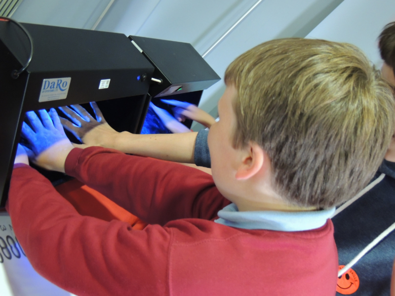 Children use a type of UV light to see how well they've cleaned their hands.