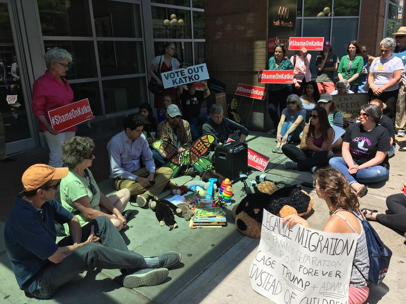 Protesters sit outside of Rep. John Katko's office in Syracuse Thursday.