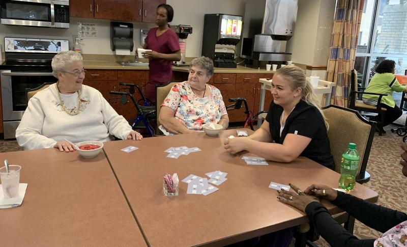 Jean Bailey, left, plays cards at Pace CNY in North Syracuse. Bailey says she felt depressed after moving to Syracuse from Vermont and the day program at Pace has helped