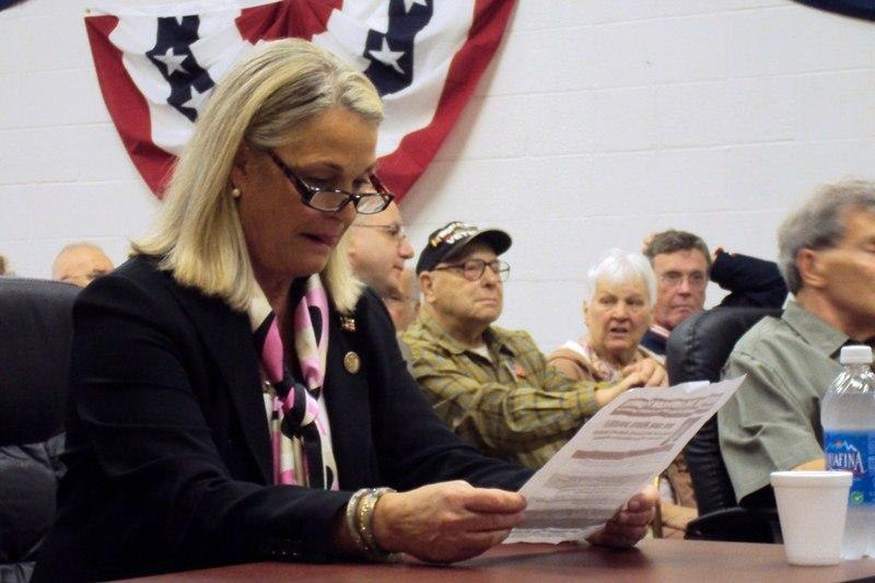 Rep. Ann Marie Buerkle (R-Onondaga Hill) reads an attack flyer before being introduced at a town hall event Friday.