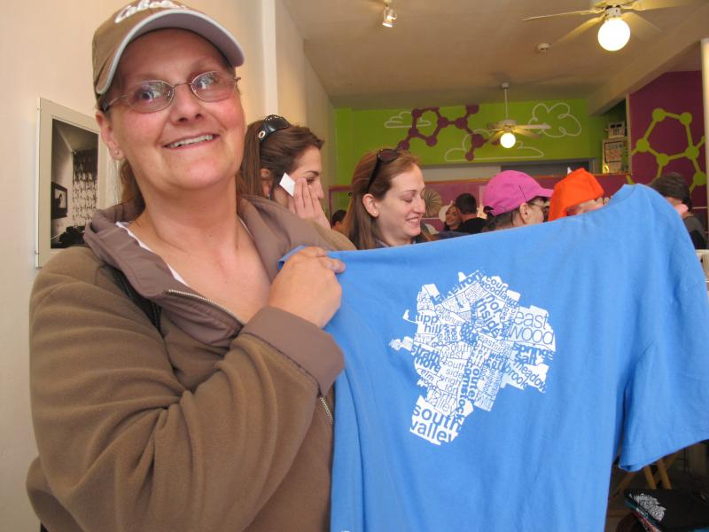 Carol Ryan shows off one of her favorite shirts at Craft Chemistry: an artistically rendered map of the neighborhoods in Syracuse. She lives in Eastwood.
