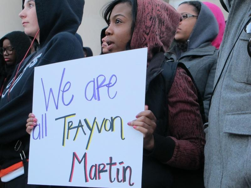 A student holds a sign at a Hoodies for Trayvon rally Monday evening at Syracuse University.