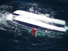 "Jason Dahl, U.S. Coast Guard swimmer swims near capsized catamaran ""Naughty Cat"" in boating accident August 5."