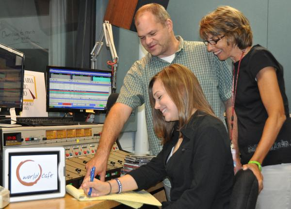 Salisbury University senior communication arts major and Delmarva Public Radio (DPR) membership assistant Michelle Malinger checks notes on the new programming schedule with DPR producer Chris Ranck and membership director Angela Byrd.