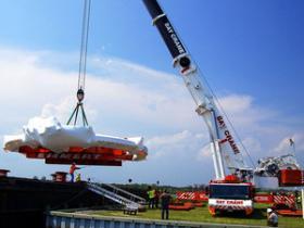 Crane readies electromagnet for transport via barge.