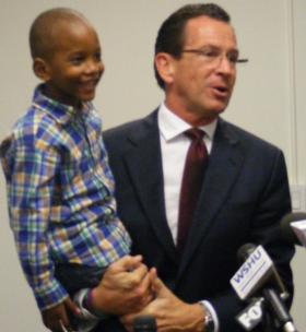 Conn. Gov. Dannel Malloy holds Michael Hall of Stratford, one of the children enrolled at the ABCD Head Start in Bridgeport