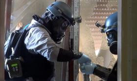In this file image taken from video obtained from the Shaam News Network Thursday, Aug. 29, 2013, members of a chemical weapons investigation team take samples from the ground in the Damascus countryside of Zamalka, Syria.