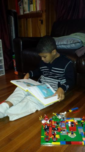 Loïc Williams, 7, of North Stamford at home reading one of his books.