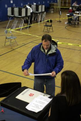 A voter prepares to insert his marked ballot into an electronic scanner to register his vote in a municipal election in North Haven, Conn., (file photo)