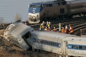 An Amtrak train, top, traveling on an unaffected track, passes a derailed Metro North commuter train, Sunday, Dec. 1, 2013 in the Bronx borough of New York. Officials are standing on a curve in the tracks where the Metro North train derailed.