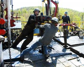 In this file photo, workers move a section of well casing into place at a Chesapeake Energy natural gas well site near BUrlington, Pa.