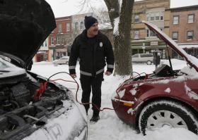 Albany firefighter Chris Kollias helps motorists jump start a vehicle on Friday, Jan. 3, 2014, in Albany, N.Y. The National Weather Service has posted winter storm warnings through Friday morning in most of the state. Temperatures are in the single digits or below zero, with the wind making it feel as cold as 20-30 below zero in some areas.