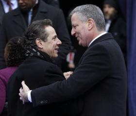 New York Governor Andrew Cuomo, left, greets New York City Mayor Bill de Blasio after his public inauguration ceremony at City Hall in New York, Wednesday, Jan. 1, 2014