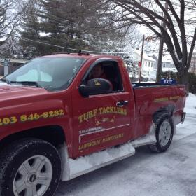 Dominick Franco plowing in Stamford. His truck was banged up behind the door in an accident overnight.