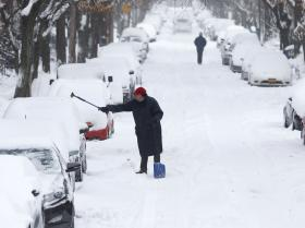 A man clears snow from a vehicle on Friday, Jan. 3, 2014, in Albany, N.Y. A winter storm slammed into the U.S. Northeast with howling winds and frigid cold, dumping nearly two feet (60 centimeters) of snow in some parts and whipping up blizzard-like conditions Friday.