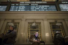 A commuter stands beneath the New Haven train line schedule display in the main hall of Grand Central Station as hundreds wait after a power problem with Metro-North Railroad's computer system caused the suspension of service on the Hudson, Harlem, and New Haven lines, Thursday, Jan. 23, 2014, in New York.