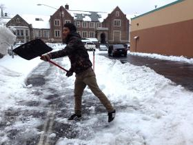 Karma Gurung shoveling snow at Natural Frontier Market in Stamford on Wednesday