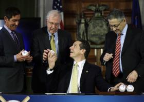 Andrew Cuomo, seated, hands out baseballs to Senate co-leader Jeff Klein, D-Bronx, from left, Sen. Kemp Hannon, R-Garden City, and Assembly Speaker Sheldon Silver, D-Manhattan, during a news conference and budget bill signing ceremony.